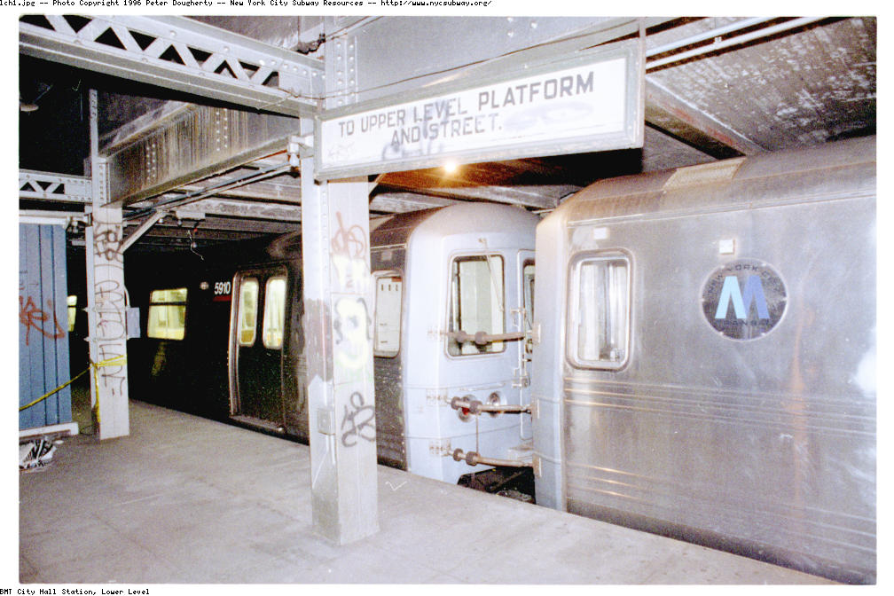 (131k, 1008x672)<br><b>Country:</b> United States<br><b>City:</b> New York<br><b>System:</b> New York City Transit<br><b>Line:</b> BMT Broadway Line<br><b>Location:</b> City Hall Lower Level<br><b>Photo by:</b> Peter Dougherty<br><b>Date:</b> 1996<br><b>Notes:</b> North end of Western platform (between tracks B3 and BM) looking West. An old-style sign pointing toward the upper level revenue-service platform is one of the only signs or markings other than graffiti on this level. This is one of two lower-level platforms never opened to the public at this station. A laid-up N train sits on track B3 awaiting the call to afternoon rush hour service. <br><b>Viewed (this week/total):</b> 0 / 14014