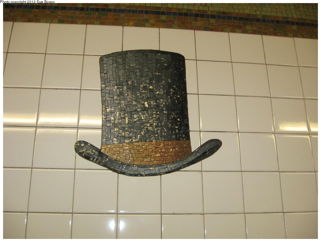 (279k, 1044x788)<br><b>Country:</b> United States<br><b>City:</b> New York<br><b>System:</b> New York City Transit<br><b>Line:</b> BMT Broadway Line<br><b>Location:</b> 23rd Street<br><b>Photo by:</b> Sue Bosco<br><b>Date:</b> 4/25/2012<br><b>Artwork:</b> <i>Memories of Twenty-Third Street</i>, Keith Godard, 2002<br><b>Notes:</b> P.T. Barnum's hat.<br><b>Viewed (this week/total):</b> 0 / 1763