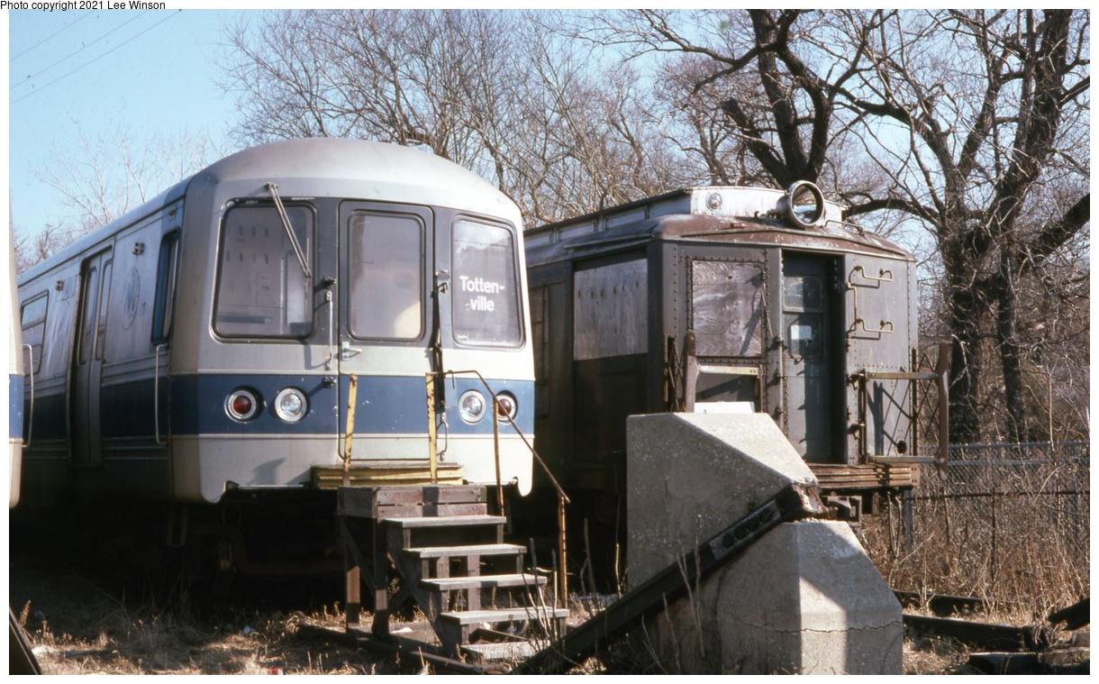 (375k, 1220x759)<br><b>Country:</b> United States<br><b>City:</b> New York<br><b>System:</b> New York City Transit<br><b>Line:</b> SIRT<br><b>Location:</b> Tottenville<br><b>Car:</b> R-44 SIRT (St. Louis, 1971-1973)  <br><b>Photo by:</b> Lee Winson<br><b>Date:</b> 2/1979<br><b>Notes:</b> SIRT R-44 with old SIRT motor at Tottenville.<br><b>Viewed (this week/total):</b> 23 / 231