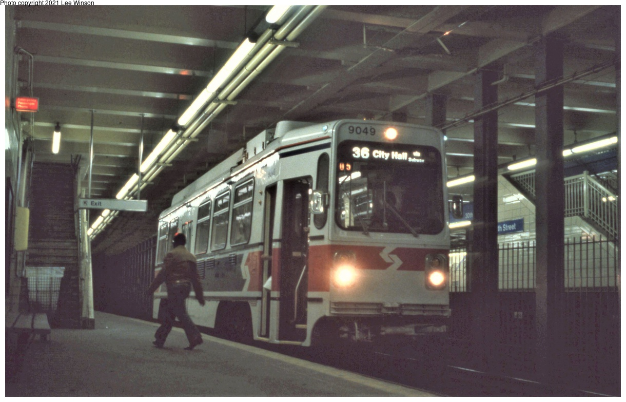 (283k, 1220x783)<br><b>Country:</b> United States<br><b>City:</b> Philadelphia, PA<br><b>System:</b> SEPTA (or Predecessor)<br><b>Line:</b> SEPTA Subway-Surface<br><b>Location:</b> 30th Street<br><b>Car:</b> SEPTA K Single-ended (Kawasaki, 1981) 9049 <br><b>Photo by:</b> Lee Winson<br><b>Date:</b> 3/1982<br><b>Notes:</b> Eastbound (inbound to Juniper Street). On the far right is the Market-Frankford subway island platform (note old style handrails). Car rollsign replaced by digital screen.   On far left wall is yellow emergency intercom box and illuminated red sign.  30th Street has a free interchange between the Subway Surface lines and the Market-Frankford line.<br><b>Viewed (this week/total):</b> 3 / 34