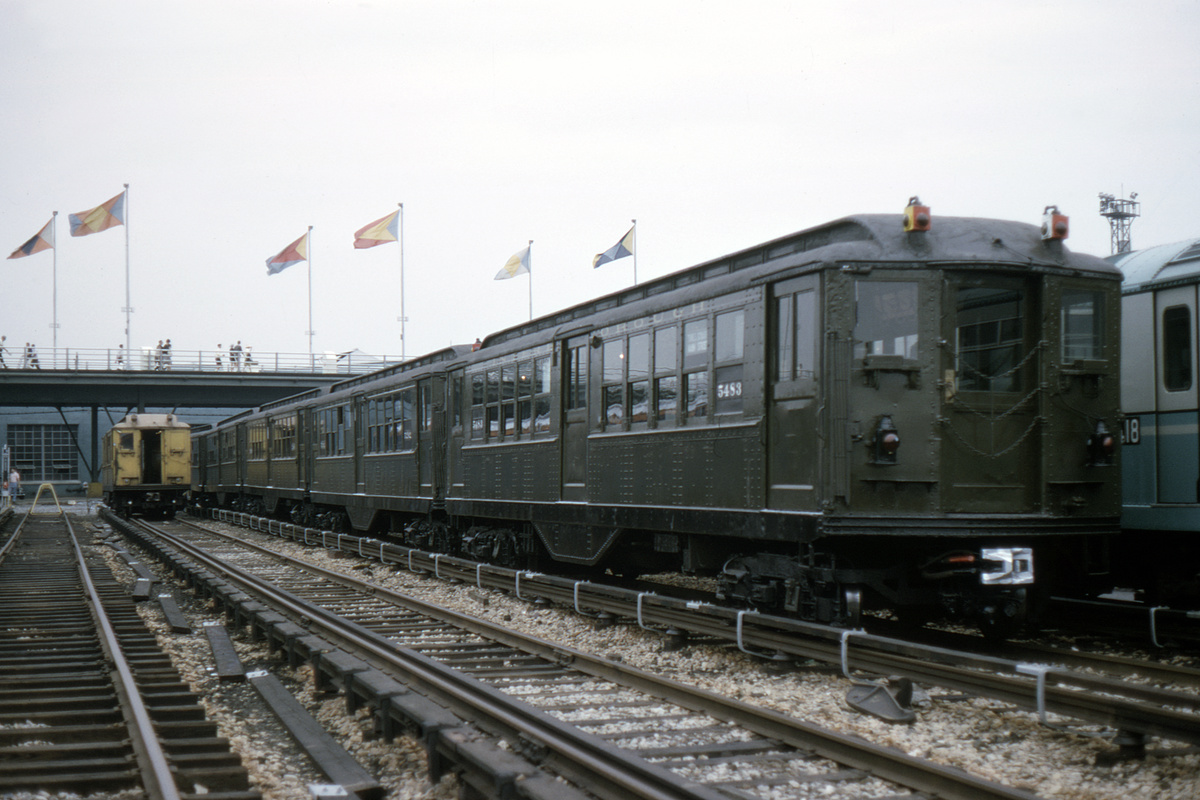 (381k, 1200x800)<br><b>Country:</b> United States<br><b>City:</b> New York<br><b>System:</b> New York City Transit<br><b>Location:</b> Corona Yard<br><b>Car:</b> Low-V (Museum Train) 5483 <br><b>Photo by:</b> Gerald H. Landau<br><b>Collection of:</b> David Pirmann<br><b>Date:</b> 7/22/1965<br><b>Notes:</b> Worlds Fair flags in background<br><b>Viewed (this week/total):</b> 1 / 3321